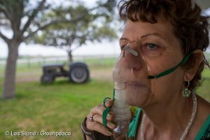 Lynn Buehring wears a breathing mask outside her home in Karnes County. She lives with her husband in the middle of three different hydrofracking wells that have been flaring since 2011. She is suffering from severe reactions to the chemicals and Hydrogen Sulfide (H2S) gas released from the wells. Her entire life has been turned upside down. A retirement place on a quiet country road has now become a nightmare. She has to wear a respirator whenever the winds blow in her direction. She is suing Marathon Oil for relief.